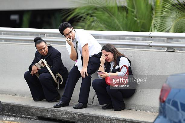 People take cover outside of Terminal 2 at Fort LauderdaleHollywood International airport after a shooting took place near the baggage claim on...