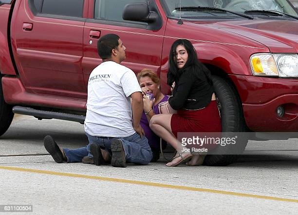 People take cover outside the Fort LauderdaleHollywood International airport after a shooting took place near the baggage claim on January 6 2017 in...