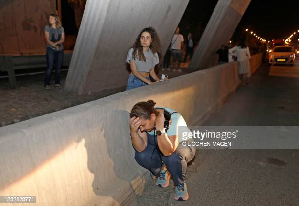 People take cover under a bridge at the entrance of Israel's central city of Tel Aviv, on May 11 after rockets were launched towards Israel from the...