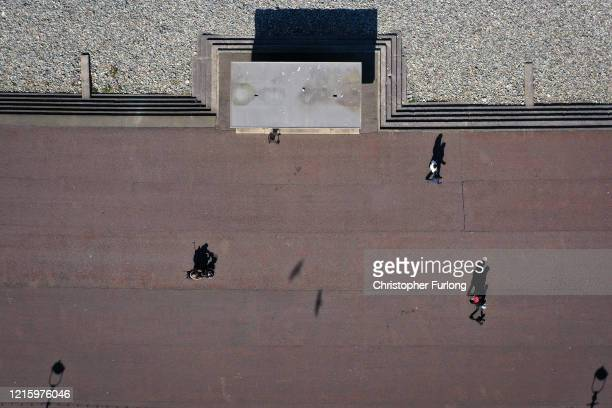 People take exercise as they observe social distancing on the near deserted promenade during the pandemic lockdown on March 31 2020 in Llandudno...