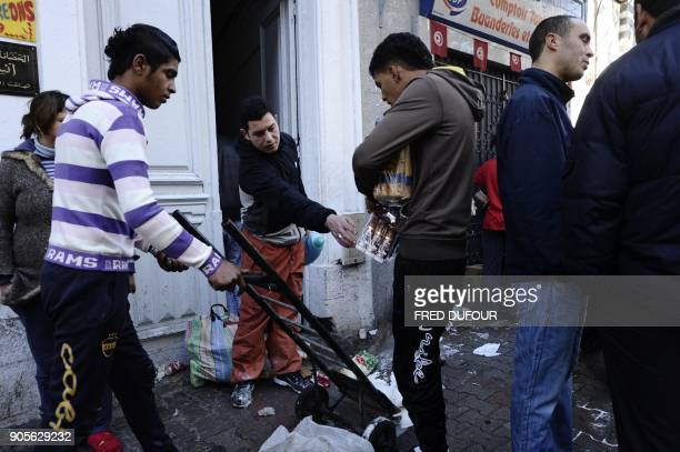People take goods from a destroyed store in Tunis on January 15 2011 There were scenes of looting overnight in the suburbs of Tunis witnesses said on...