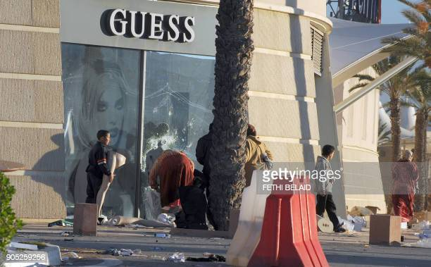 People take goods from a looted supermarket on January 15 2011 in La Gazella city near Tunis Tunisia's speaker of parliament took power on today amid...