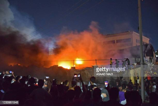 People take images of flames as a massive fire engulfs the coronavirus isolation ward of Al-Hussein hospital in the southern Iraqi city of Nasiriyah,...