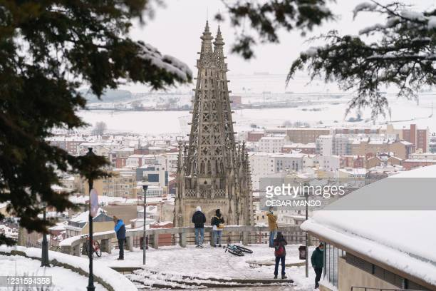 People take images of the cathedral from a viewpoint of the city after a heavy snowfall in Burgos, northern Spain, on March 8, 2021.