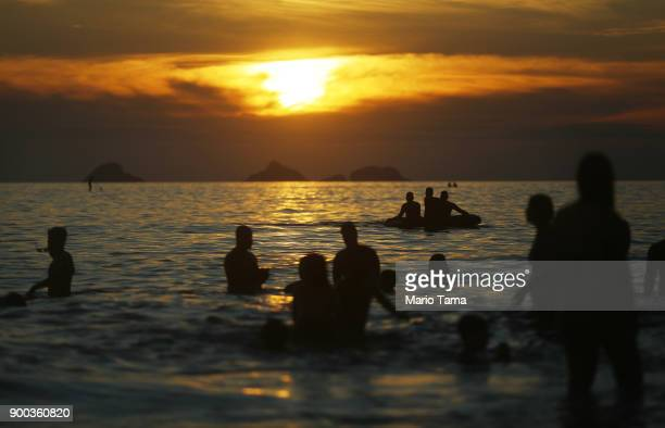 People take in the first sunset of 2018 along Ipanema beach on January 1 2018 in Rio de Janeiro Brazil Fireworks were launched earlier in Rio and...
