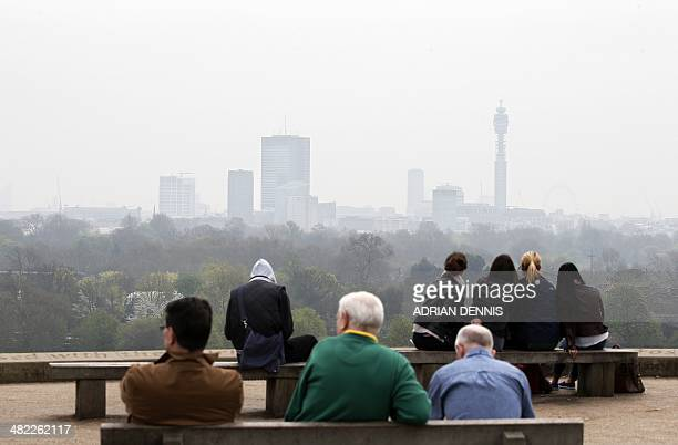 People take in the view at the top of Primrose Hill in London on April 3 as the city below lies shrouded in pollution A combination of local...