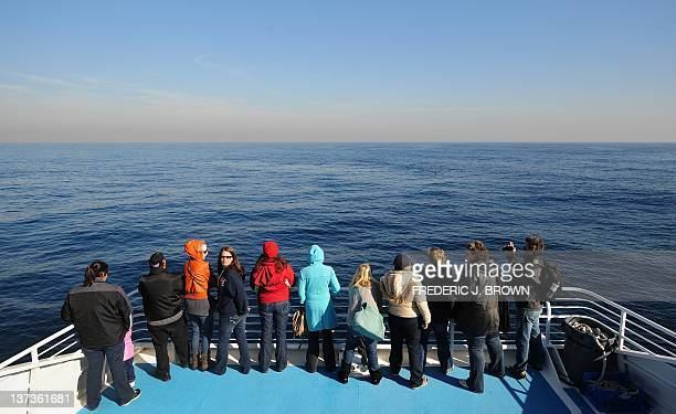 People take in the view from the front of a boat in the Pacific Ocean hoping for a glimpse of the Fin whale which grows up to nearly 27metres...