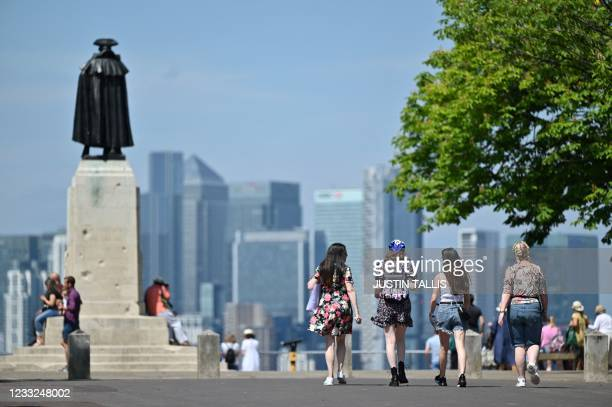 People take in the view of the City of London skyline during a warm spell, in Greenwich Park, south east London on June 3, 2021. - Much of Britain...