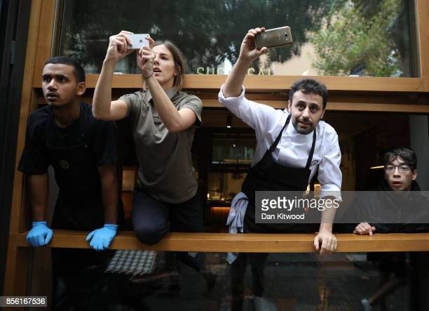 People take mobile phone pictures from a window as people protest police trying to control the area as an attempt is made to cast ballots at a...