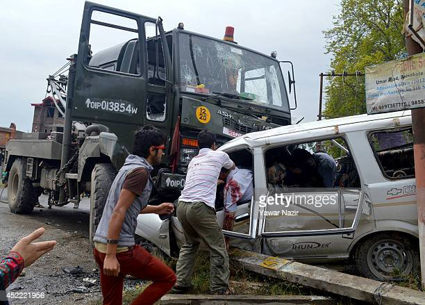 People take out the dead and wounded from a cab after it was hit by an Indian Army vehicle killing at least six people July 16 2014 in Zaina Koot on...