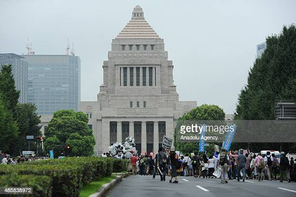 People take part a major protest labeled as a nationwide movement for 1 million people organized near the National Diet Building on August 30 in...