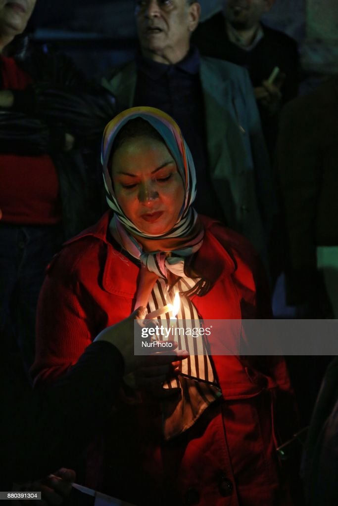 People take part during a candlelight vigil as they hold national flags for victims of a Friday mosque attack at the Journalists Syndicate, in Cairo, Egypt, Monday, Nov. 27, 2017. Friday's assault was Egypt's deadliest attack by Islamic extremists in the country's modern history, a grim milestone in a long-running fight against an insurgency led by a local affiliate of the Islamic State group. At center, Abdel Mohsen Salama, the head of the Press Syndicate.