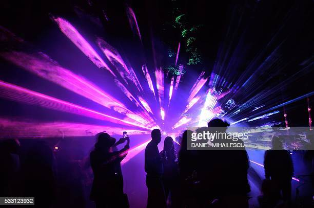 People take part in 8th edition of Abduction Beamz night laser party in a forest near Balotesti village Romania on May 21 2016 / AFP / DANIEL...