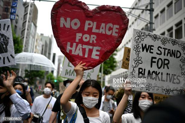 People take part in a Black Lives Matter protest march in central Tokyo on June 14, 2020. - The protests are part of a worldwide movement following...