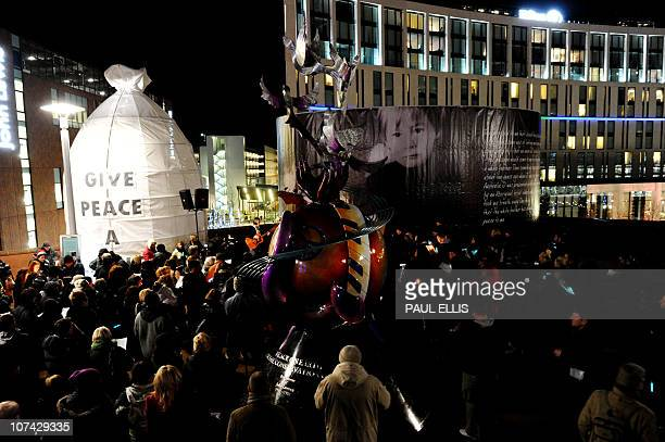 People take part in a candle lit vigil in Liverpool northwest England on December 8 2010 to mark the 30th anniversary of the death of former Beatles...