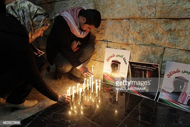 People take part in a candlelight vigil in the capital Amman on February 7 to express solidarity with the Jordanian pilot recently murdered by the...