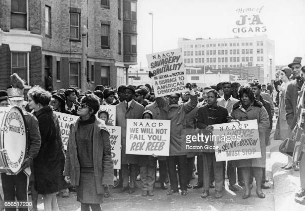People take part in a civil rights demonstration holding signs expressing support for the NAACP on Columbus Avenue in Boston on Mar 14 1965