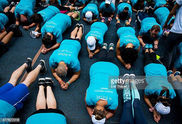 People take part in a Fitbit lunchtime workout event outside the New York Stock Exchange during the IPO debut of the company on June 18 2015 in New...