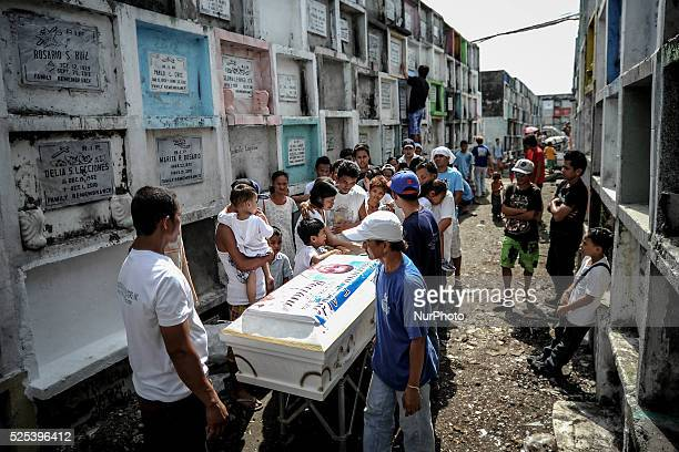 People take part in a funeral ceremony at the municipal cemetery of Navotas city, north of Manila, Philippines, October 28, 2014. Millions of...