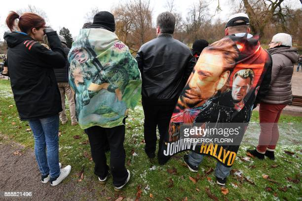 People take part in a gathering in tribute to late French singer Johnny Hallyday on the day of his funeral on December 9 2017 at the Orangerie park...
