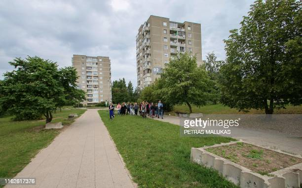 People take part in a guided tour to the places where the HBO series Chernobyl was shot in the district Fabijoniskes in Vilnius on July 13 2019 Fans...
