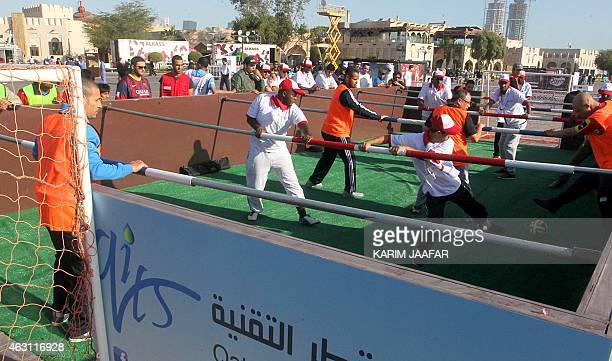 People take part in a human Foosball game during the Qatar National Sport Day in the capital Doha on February 10 2015 More than a million Qataris...