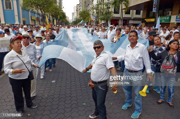 People take part in a march for peace against a fuel price hike ordered by the government to secure an IMF loan in front of riot police in Guayaquil...
