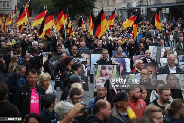 People take part in a march of silence organized by the right-wing Alternative for Germany political party and carry German flags and supposed...