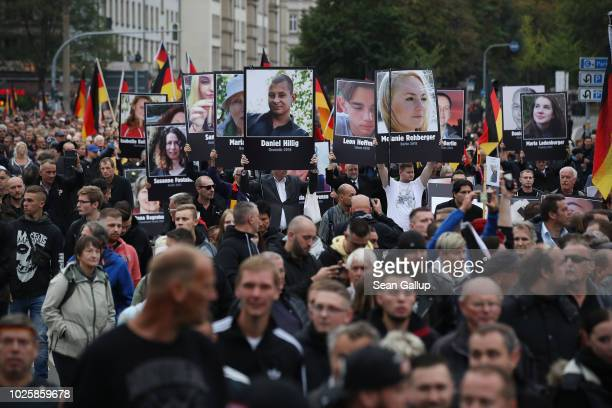 People take part in a march of silence organized by the right-wing Alternative for Germany political party and carry German flags and portraits of...