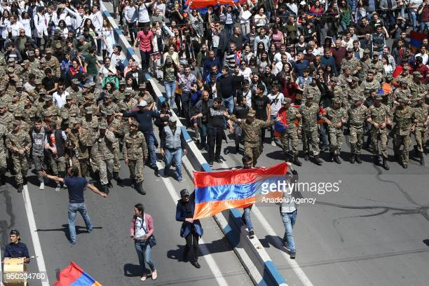 People take part in a march protest against the election of former Armenian President Sargsyan as the Prime Minister by the National Assembly of...