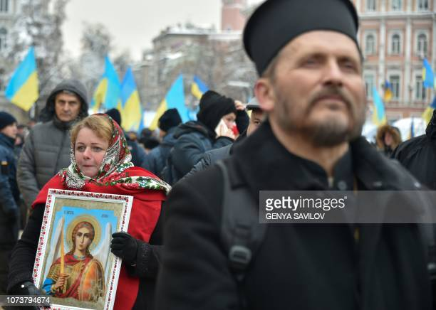 People take part in a meeting in Kiev Ukraine on December 15 outside of St Sophia cathedral ahead of historic synod held to establish an Orthodox...