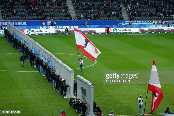 TOPSHOT People take part in a performance next to a mockup of the former Berlin Wall prior to the German first division Bundesliga football match...