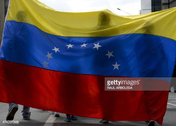People take part in a protest against the government of Venezuelan President Nicolas Maduro with a Venezuelan national flag in Caracas, on February...