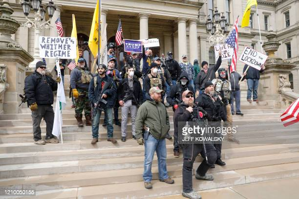 "People take part in a protest for ""Michiganders Against Excessive Quarantine"" at the Michigan State Capitol in Lansing, Michigan on April 15, 2020. -..."
