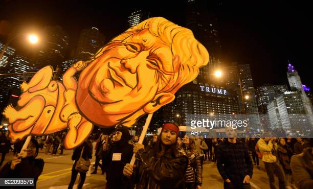 TOPSHOT People take part in a protest near the Trump tower against Presidentelect Donald Trump in Chicago Illinois on November 9 2016