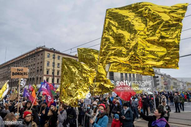 People take part in a protest rally in solidarity with migrants who have been pushed back at Poland's border with Belarus in Warsaw, October 17,...