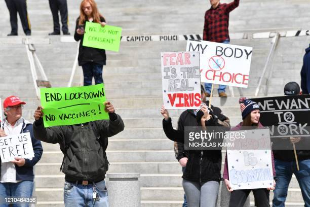 People take part in a reopen Pennsylvania demonstration on April 20 2020 in Harrisburg Pennsylvania Hundreds of people including lawmakers gathered...