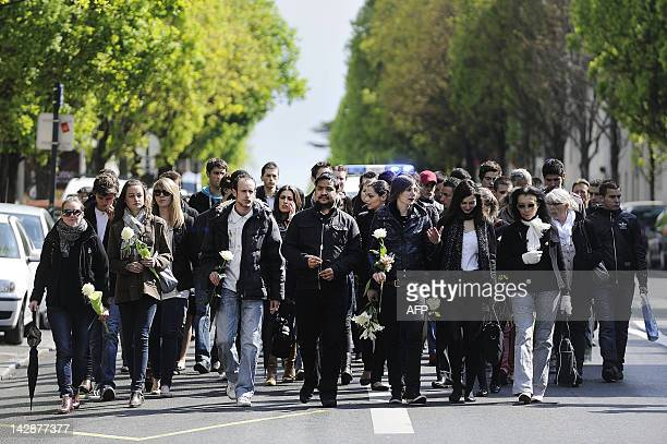 People take part in a silent march on April 14 2012 in the streets of Nantes western France to mark the first anniversary of the murders of the...