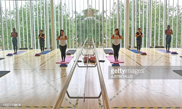 People take part in a socially distanced yoga class at Kensington Leisure Centre in west London on July 25, 2020 as novel coronavirus lockdown...