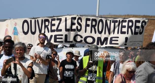 People take part in a 'solidarity' march in support of migrants in Calais on July 7 2018 The banner reads 'Open borders welcome' Several hundred...