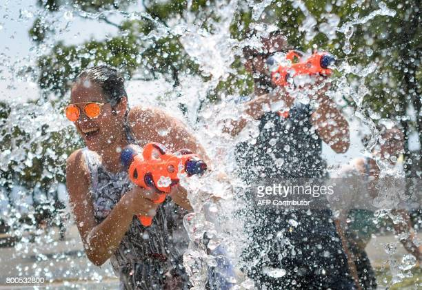TOPSHOT People take part in a tenminute flashmob on June 24 2017 at a fountain in Lausanne to cool off as heatwave scorches Europe / AFP PHOTO /...