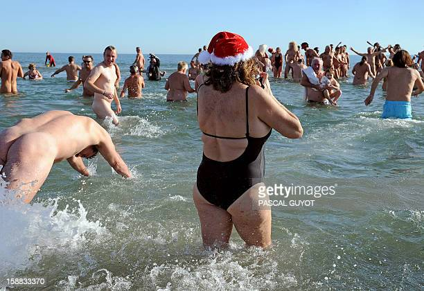 People take part in a traditional bath to mark the end of the year on December 31 2012 on a nudist beach in Le Cap d'Agde southern France Five...