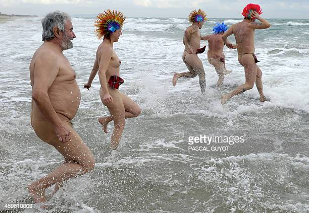 People take part in a traditional sea bathing to mark newyear's end on December 31 2013 on a nudist beach in Le Cap d'Agde southern France AFP PHOTO...