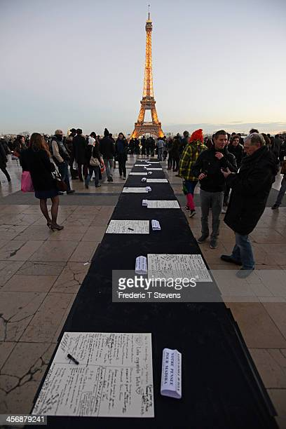 People take part in a tribute to former South African President Nelson Mandela on the Parvis des droits de l'homme on December 15 in Paris France Mr...