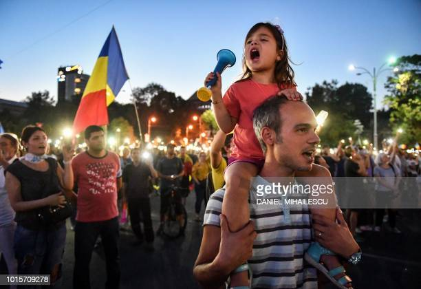 People take part in an anti government protest in front of the Government headquarters in Bucharest on August 12, 2018. - Thousands gathered Sunday...