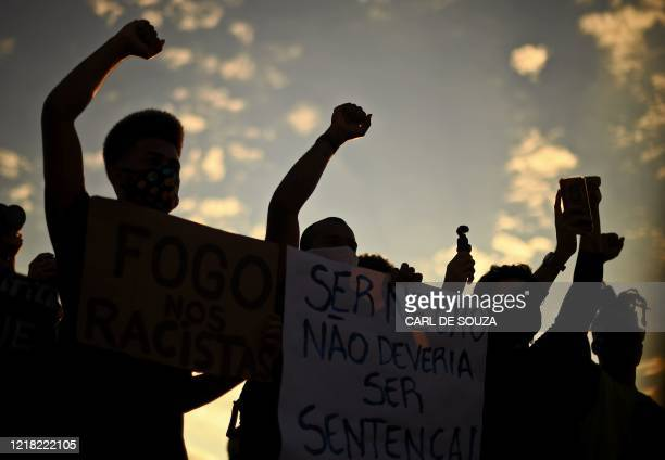 People take part in an antiracism demonstration in which protesters also shouted slogans against Brazilian President Jair Bolsonaro in Rio de Janeiro...
