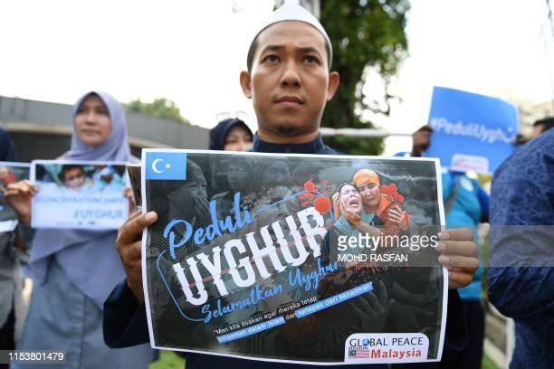 People take part in an event in front of the Chinese embassy in Kuala Lumpur on July 5 2019 in solidarity with the Uighur community in China and to...