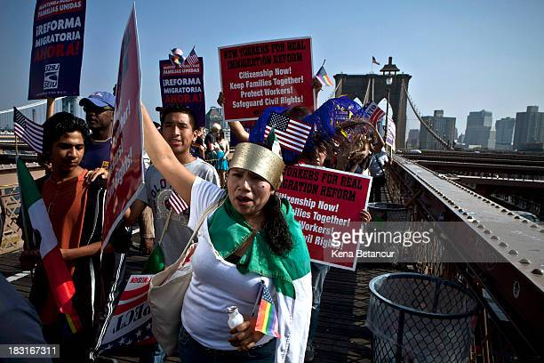 People take part in an immigration reform march across the Brooklyn bridge on October 5 2013 in New York City Immigration groups marched in 100...