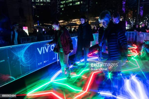 People take part in an interactive light installation during the Vivid Festival on June 13 2017 in Sydney Australia Vivid Sydney is an annual...