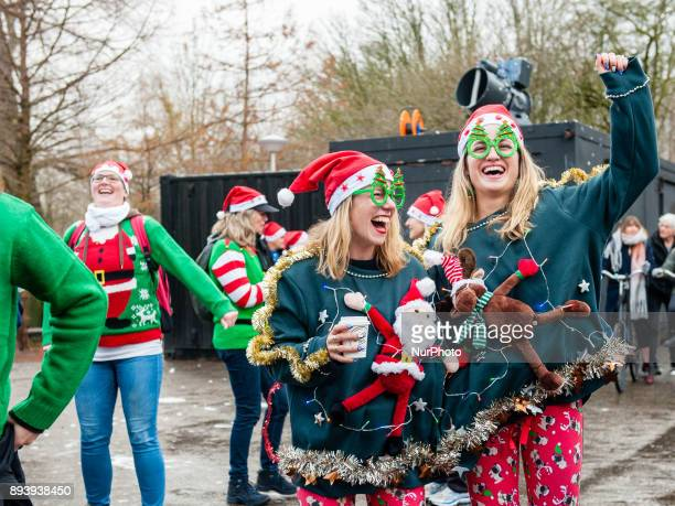 People take part in an Ugly Christmas Sweater Run on December 16 2017 in The Vondelpark in Amsterdam Netherland During this 5K run people have the...